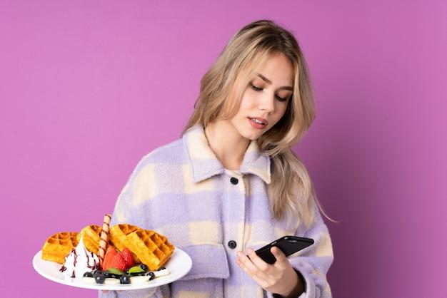 De holdingswafels van het tienermeisje op purpere muur die een bericht met mobiel verzenden