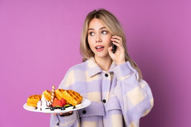 De holdingswafels van het tienermeisje op purpere muur die een gesprek met de mobiele telefoon met iemand houden