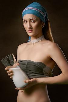De holdingswaterkruik van de vrouw van glas met melk