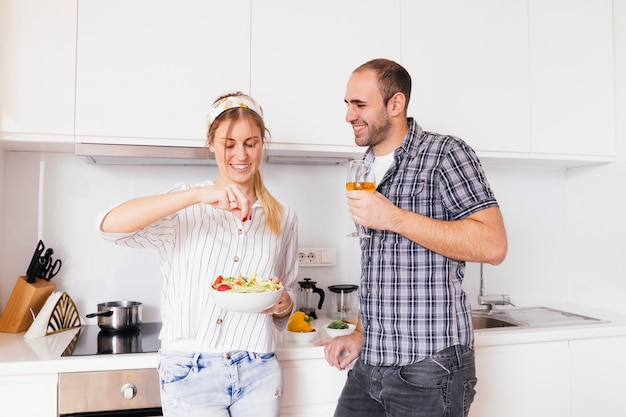 De holdingswijnglas van de man in hand bekijkend haar glimlachende vrouw die het zout in salade kruiden