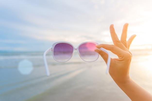 De holdingszonnebril van de vrouwenhand over overzees en zandig strand binnen tijdens zonsondergang