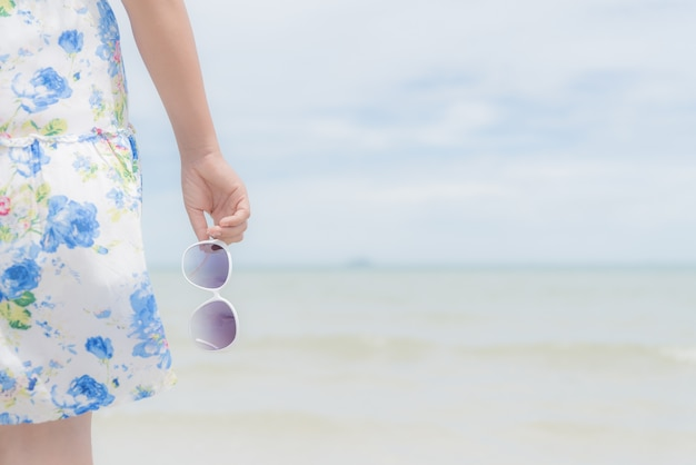 De holdingszonnebril van de vrouwenhand over overzees en zandig strand op achtergrond voor de zomerconcept.