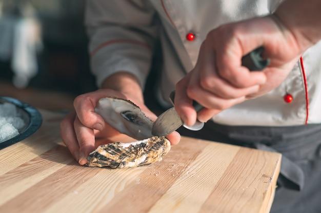 De holle en platte oesters openen. chef-kok opent oesters in het restaurant.