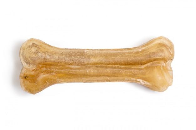 De hond kauwt beenderen die op wit worden geïsoleerd