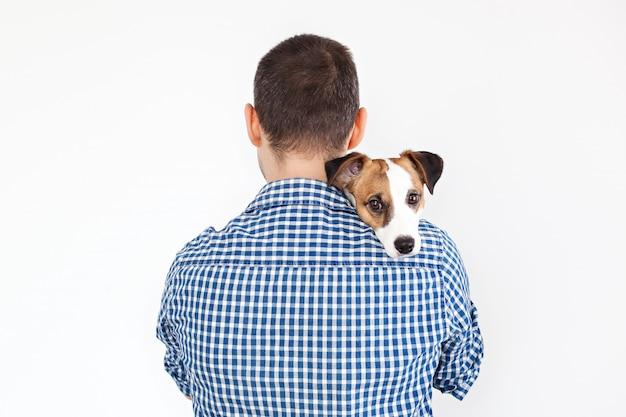 De hond ligt op de schouder van zijn baasje. jack russell terrier in de handen van zijn eigenaar op wit. het concept van mensen en dieren. de man houdt zijn hond in zijn armen en speelt met hem.
