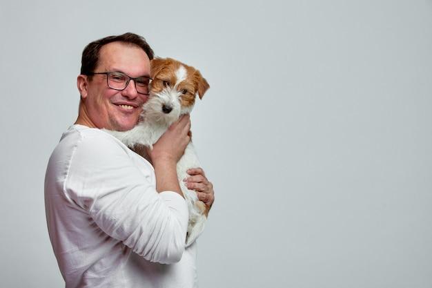 De hond ligt op de schouder van zijn baasje. jack russell terrier in handen van zijn eigenaar op witte muur. het concept van mensen en dieren. t
