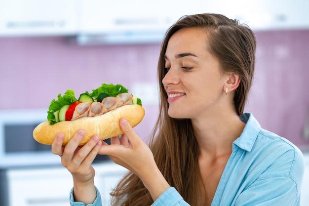 De hongerige etende vrouw eet eigengemaakte sandwich. voedselverslaving. genieten van eten