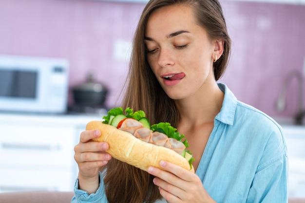 De hongerige etende vrouw eet eigengemaakte sandwich