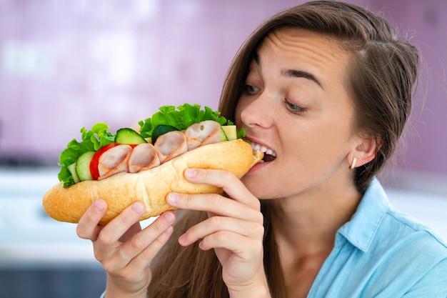 De hongerige vrouw eet eigengemaakte sandwich. voedselverslaving. gulzigheid en overgewicht door schadelijk fastfood en ongezond eten