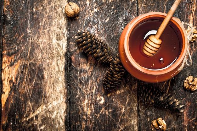 De honing in de pot met de noten en kegels op houten tafel.