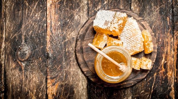 De honing in de pot met de noten op houten tafel.