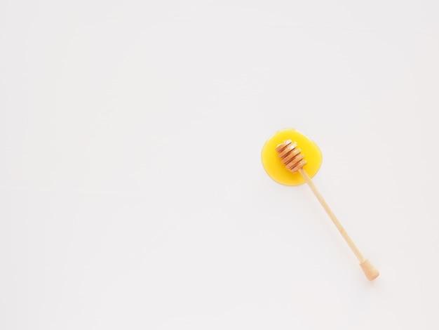 De honingplons met houten lepel plat lag geïsoleerd op wit