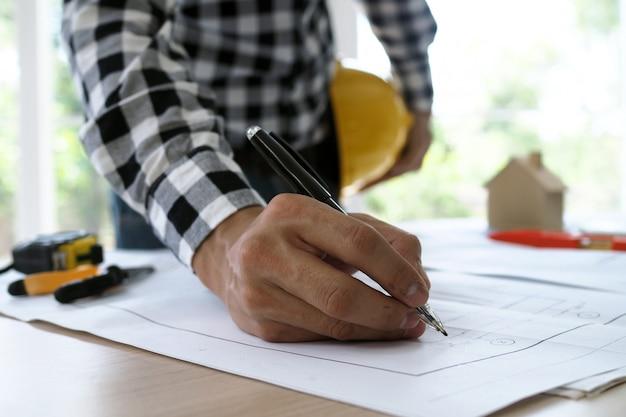 De hoofdingenieur overhandigt de pen om de blauwdruk van het gebouw te controleren