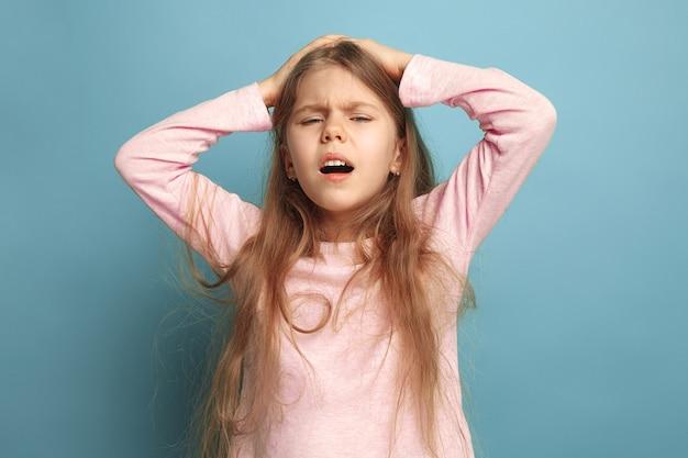 De hoofdpijn. het trieste tienermeisje met hoofdpijn of pijn op een blauwe studioachtergrond. gezichtsuitdrukkingen en mensen emoties concept. trendy kleuren. vooraanzicht. halve lengte portret