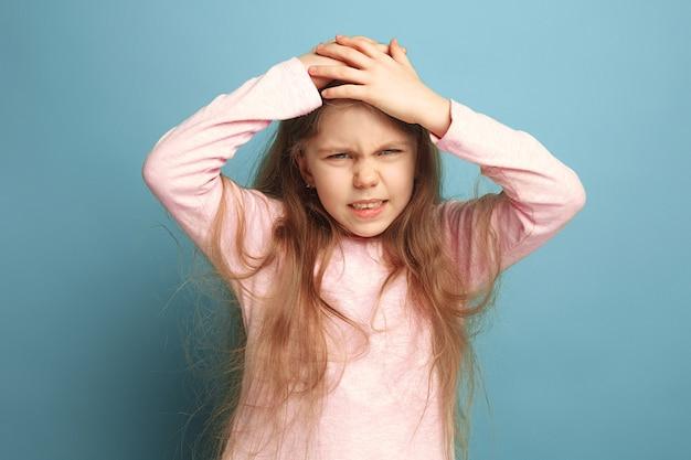 De hoofdpijn. tiener meisje op een blauw. gezichtsuitdrukkingen en mensen emoties concept
