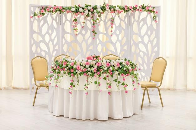 De hoofdtafel van de pasgetrouwden, versierd met een bloemige compositie en een boog in pastelkleuren