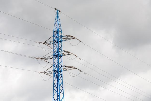 De hoogspanningsmast van de elektriciteit die tegen wolkenhemel wordt gesilhouetteerd