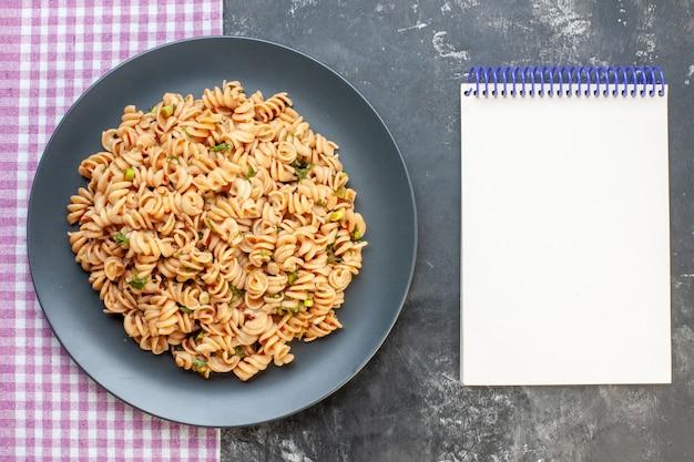 De hoogste deegwaren van meningsrotini op ronde plaat op roze wit geruit tafelkleed kladblok op de donkere foto van het oppervlaktevoedsel