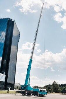 De hoogste en grootste blauwe autokraan staat opgesteld op een platform naast een groot modern gebouw.