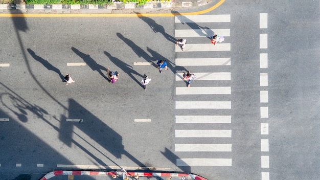 De hoogste luchtmening van groepsmensen loopt bij straatstad met voetzebrapad in de weg van het vervoersverkeer.
