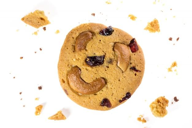 De hoogste mening van chocoladeschilferkoekjes en cashewnoten die op wit worden geïsoleerd, legt vlak van zoet en dessert met rozijnenzaden