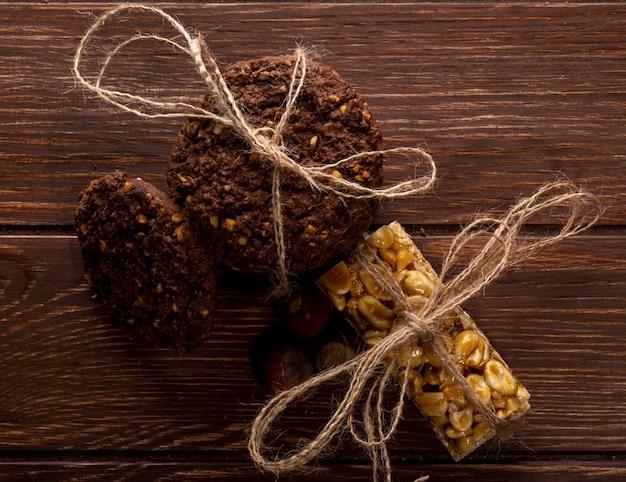 De hoogste mening van chocoladeschilferkoekjes met graangewassennoten en cacao bond met een kabel op houten