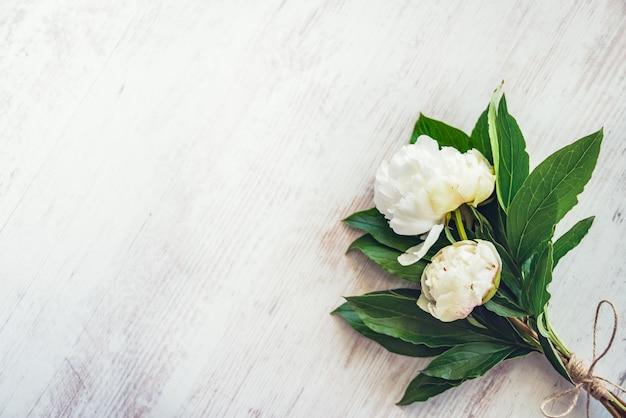 De hoogste mening van een boeket van witte pioenen bloeit over witte houten plattelander, copyspace.