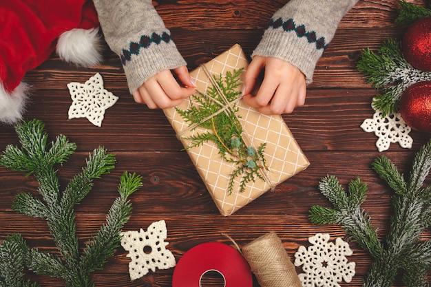 De hoogste mening van een vrouw overhandigt met een kerstmisgift op houten