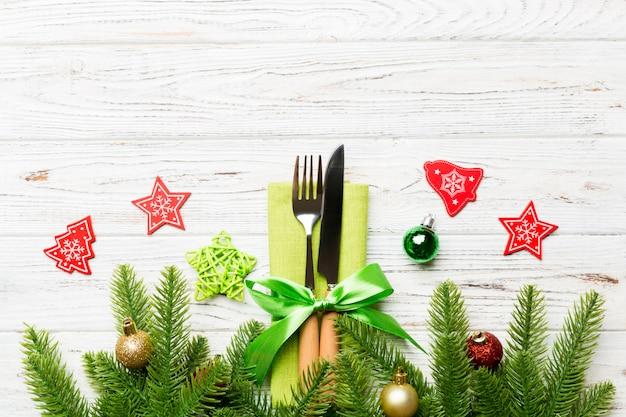 De hoogste mening van kerstmisdecoratie op houten, vork en mes op servet klopte met lint en lege ruimte