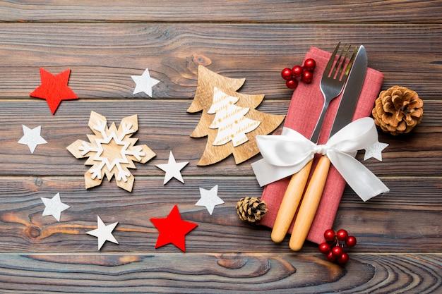De hoogste mening van nieuwjaardiner op houten, feestelijk bestek op servet met kerstmisdecoratie en speelgoed, sluit omhoog van familie