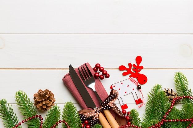 De hoogste mening van tafelgereedschap klopte met lint op servet op houten achtergrond. kerstdecoraties en rendieren met lege ruimte. nieuwjaars vakantie