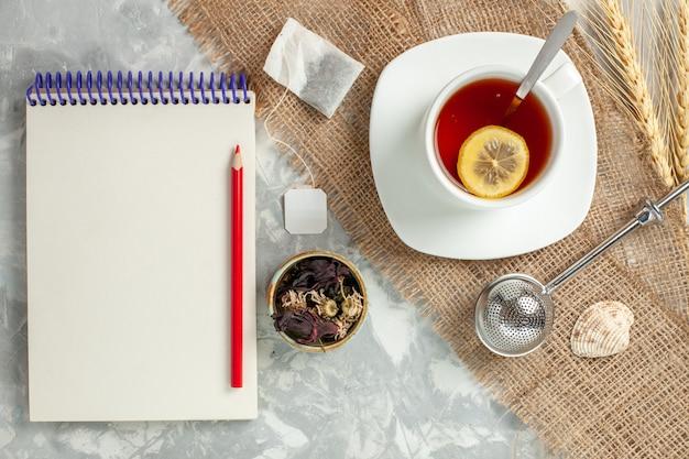 De hoogste meningskop thee met citroenplak en blocnote op witte muur drinkt de citroen van het theefruit