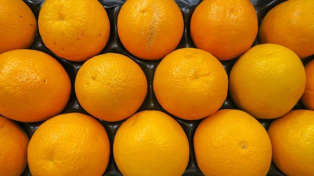 De hoogste meningstextuur van verse sinaasappelen bracht doos aan klaar om in supermarkt, achtergrond te verkopen