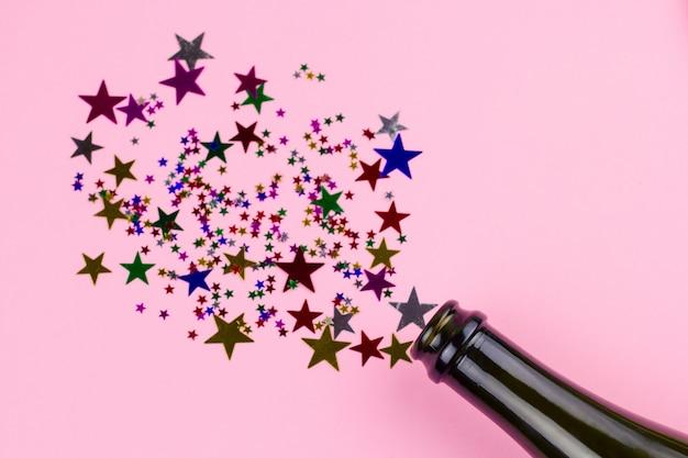 De hoogste meningsvlakte legt fles met kerstmisdecoratie van confettiensterren
