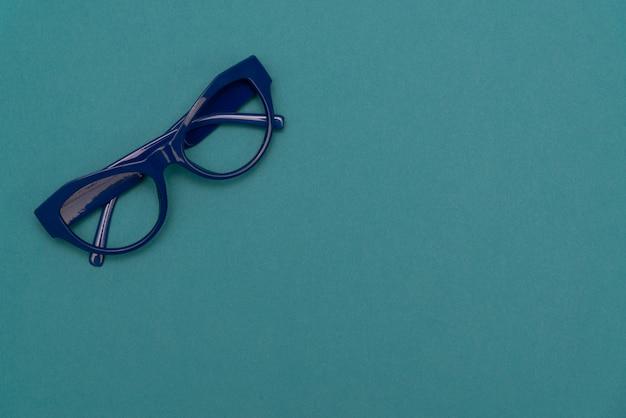 De hoogste meningsvlakte legt, moderne blauwe oogglazen op pastelkleurdocument achtergrond