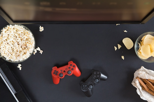 De hoogste vlakke mening van gamer accessorises en snackskader, legt op zwarte achtergrond met copyspace. joystick en gamepad, toetsenbord, gameconsole, muis, mobiele telefoon, bier, chips en popcorn.