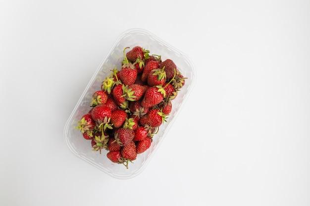 De hoogste vlakke mening van rijpe aardbeien in een plastic dienblad op een grijze achtergrond, lag