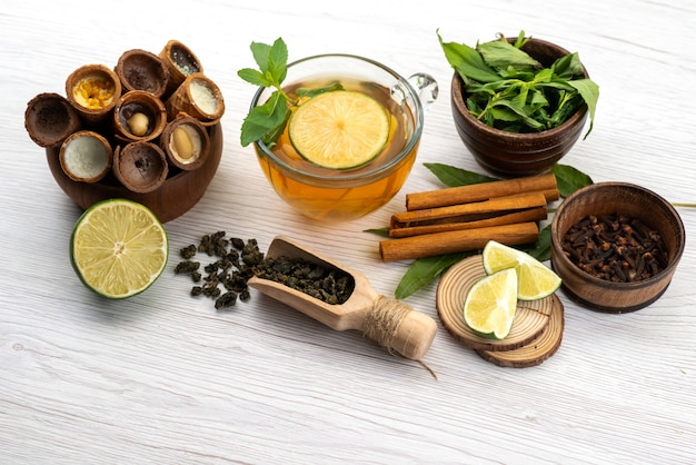 De hoorns van een vooraanzichtijs samen met citroenenkop thee en munt op wit, het roomijs van het fruitdessert