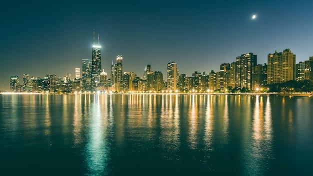 De horizon van chicago bij nacht met bezinningen