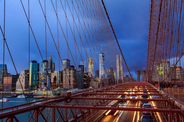De horizon van manhattan van de brug van brooklyn bij schemer