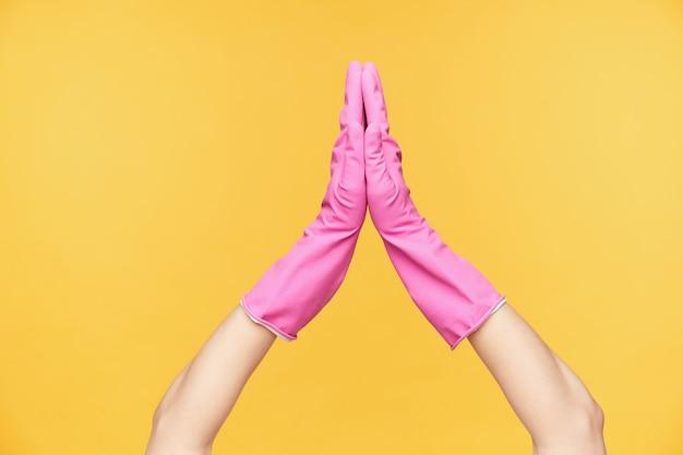 De horizontale foto van het opgeheven wijfje dient rubberhandschoenen in die handpalmen bij elkaar houden terwijl wordt geïsoleerd over oranje achtergrond. lichaamstaal en gebaren concept