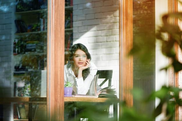 De horizontale foto van jong meisje dat buiten kijkt werpt vensterglas. kort zwart haar hebben, lichte make-up voor overdag. zittend op houten tafel op witte muurmuur. er geconcentreerd uitzien, zich ontspannen voelen.