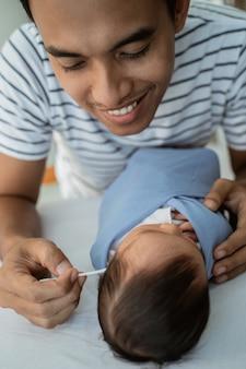 De houdende van vader maakte de oren van het babymeisje schoon