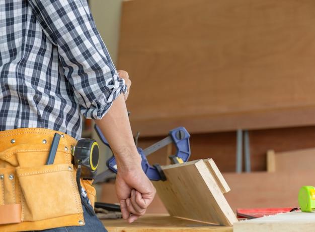 De houtbewerker van de timmermansmens steekt de mouwen op, craftsman-concept.