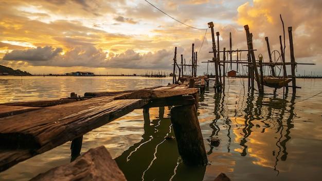 De houten boot bij pijler in thailand, het werd opgeheven boven water.