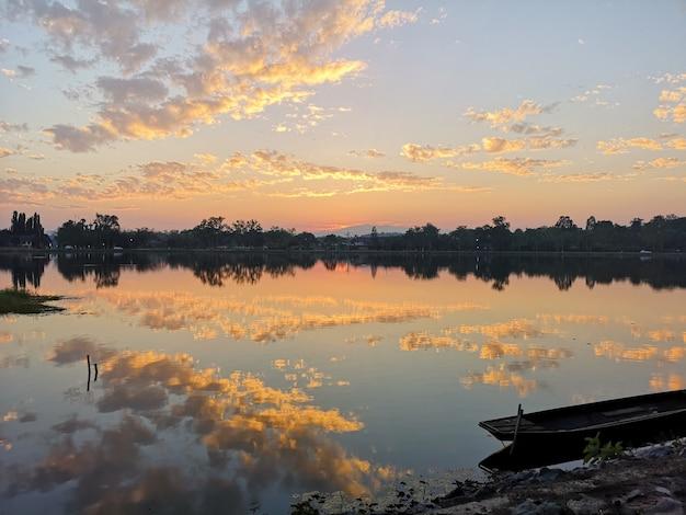 De houten boot op de rivier en de hemel betrekken zonsondergang