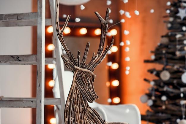 De houten decoratieve herten sluiten omhoog. modern kerstmisbinnenland dat in rustieke stijl wordt verfraaid.