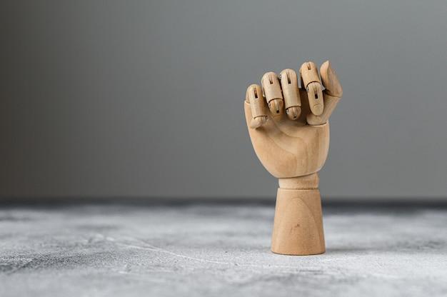 De houten hand is in een vuist gebald. het concept van communicatie.