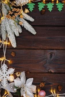 De houten kerstachtergrond is versierd met feestelijk decor, lantaarns, sneeuwvlokken en takken van de kerstboom.