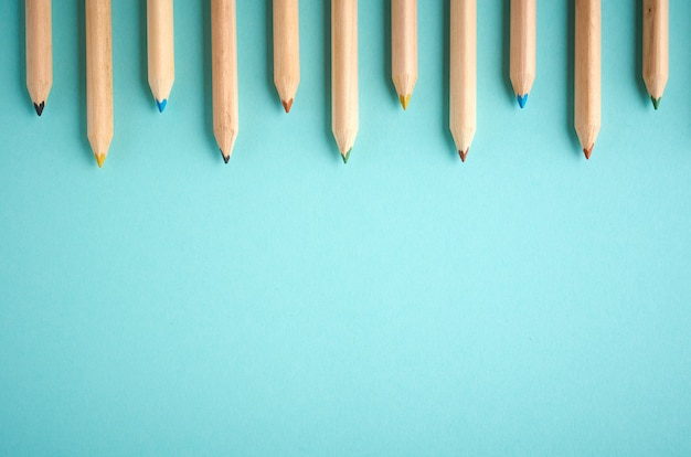 De houten kleurenpotloden op blauwe ackground met vlakke copyspace, leggen